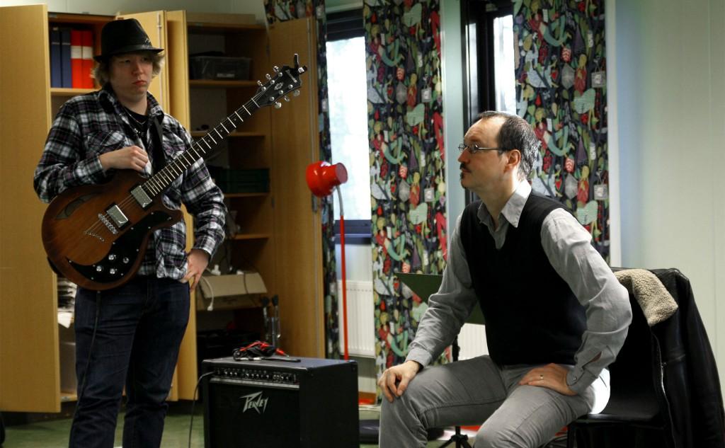 Peter Asplund sitter på en stol till höger. Till vänster en deltagare med gitarr.