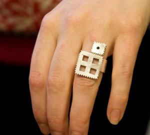 En silverring uppbyggd av två kvadrater, den ena mindre än den andra.
