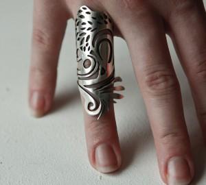Lång silverring som går över 3/4 av ett finger. Runda mönster.