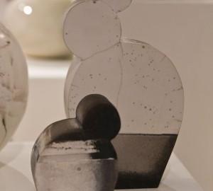 Två abstrakta, rakubrända, keramikskulpturer med platta sidor men rundande former.