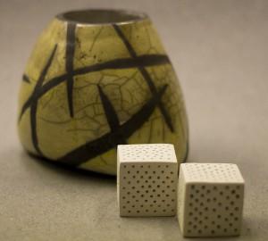 En gröngul keramikvas och två vita kuber i keramik