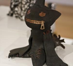 Svart katt i keramik, med dragkedja till mun.