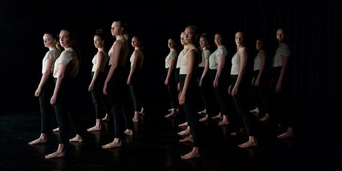 En grupp dansare i scenljus halvt vända mot kameran.