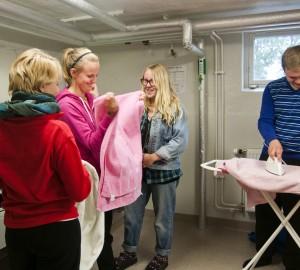 Fyra deltagare tar ut och stryker tvätt i tvättstugan.