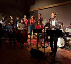 Ett stort band - partybandet - spelar. Det är en hel blåssektion, komp, trummor och sångare i bild.