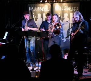 En jazzensemble spelar på en mörk scen.