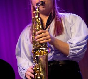 En saxofonist spelar med slutna ögon.