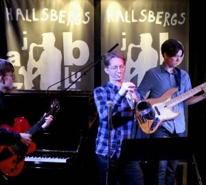 En del av en ensemble - gitarr, trumpet och bas - spelar på en mörk scen.