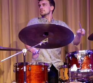 En trummis mitt upp i spelandet, håller ögonkontakt med någon utanför bild.