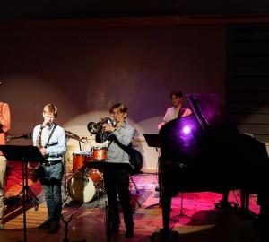 En jazzensemble, inklusive flygel, spelar i en stor sal.