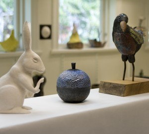 Vit keramikkanin, blå keramikvas och fågel i keramik
