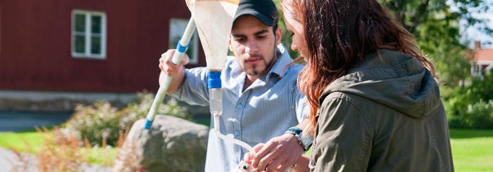 Två deltagare genomför en laboration vid dammen.