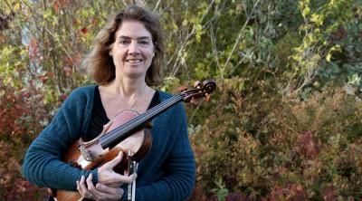 Porträttbild Kate Pelly. Kate står framför en buske och håller i en fiol.