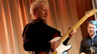 Peter Alsterlund spelar gitarr vid en lärarkonsert på Kävesta.
