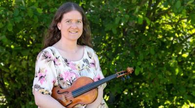 Silvia framför en grönskande buske, med en violin i famnen.
