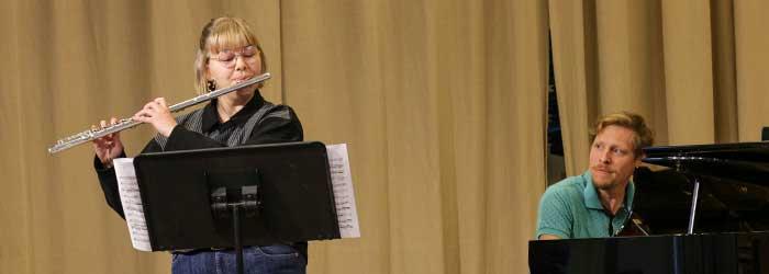 En flöjtist som kompas på piano.