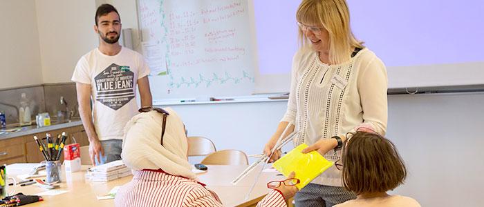 En lärare delar ut ett paket till en deltagare i slöja.