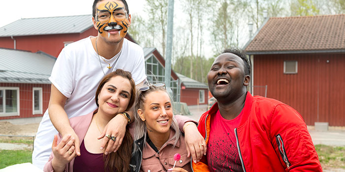 Fyra deltagare kramar om varandra och skrattar. En har ansiktsmålning och en har en godisklubba.