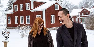 Andreas står bredvid skolans rektor Lisa. Det är vinter och snö. I bakgrunden syns en röd träbyggnad med vita knutar, skolans museum.