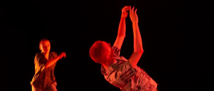 I förgrunden en person som är vänd bort från kameran, kröker ryggen och sträcker händerna i luften. Från vänster kommer en andra person springande.