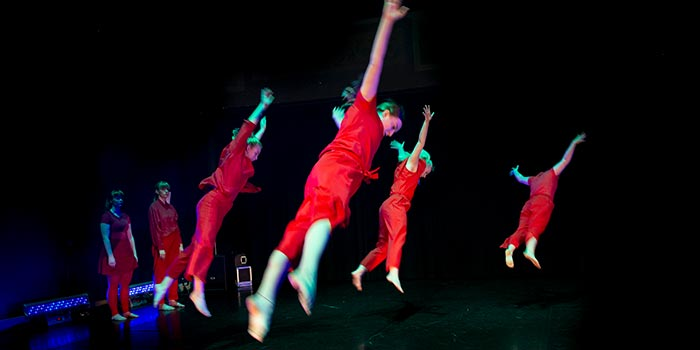 """Fyra dansare """"hänger i luften"""" med utsträcka ben och armar."""