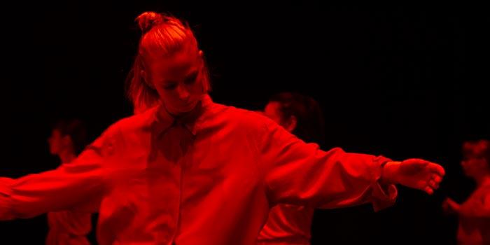 Dansare i starkt rött sken med utsträckta armar och nedböjt huvud.
