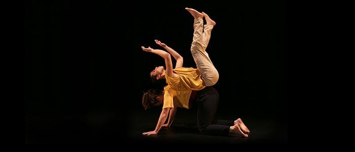 Två dansare balanserar på varandra. En står på alla fyra. En balanserar på den andra, liggande på rygg.