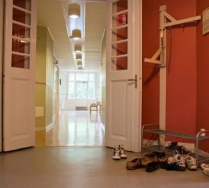 En bild av en korridor i huset Internatet. I förgrunden skoställ.