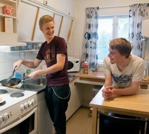 Två deltagare lagar pannkakor i köket i Lilla Huset.