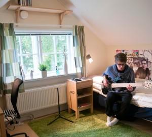 Deltagare sitter på sängen i sitt rum i Lilla Huset och spelar bas.