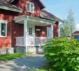 Lilla huset sett utifrån, en röd tvåplansvilla med veranda vid dörren.