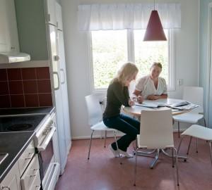 Två deltagare sitter och arbetar vid matbordet i köket i Villan.