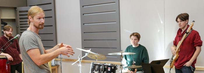 En lärare pratar med tre deltagare som spelar congas, trummor och bas.