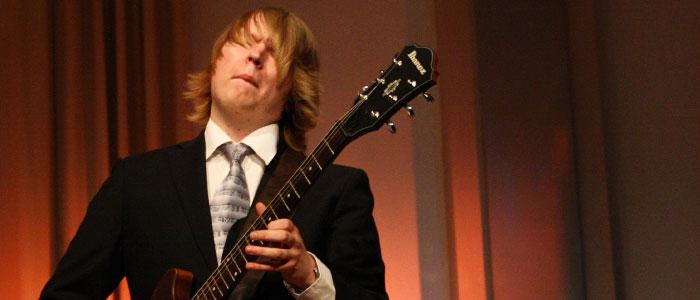 """Nicklas Boman spelar gitarr vid konserten """"Musik från när och fjärran""""."""
