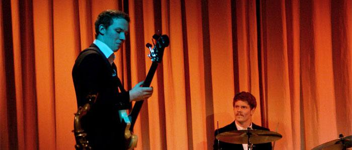 Rasmus Eriksson till höger i kostym, spelandes bas.