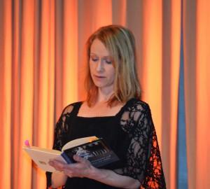 En person reciterar ur en bok, med boken i handen.