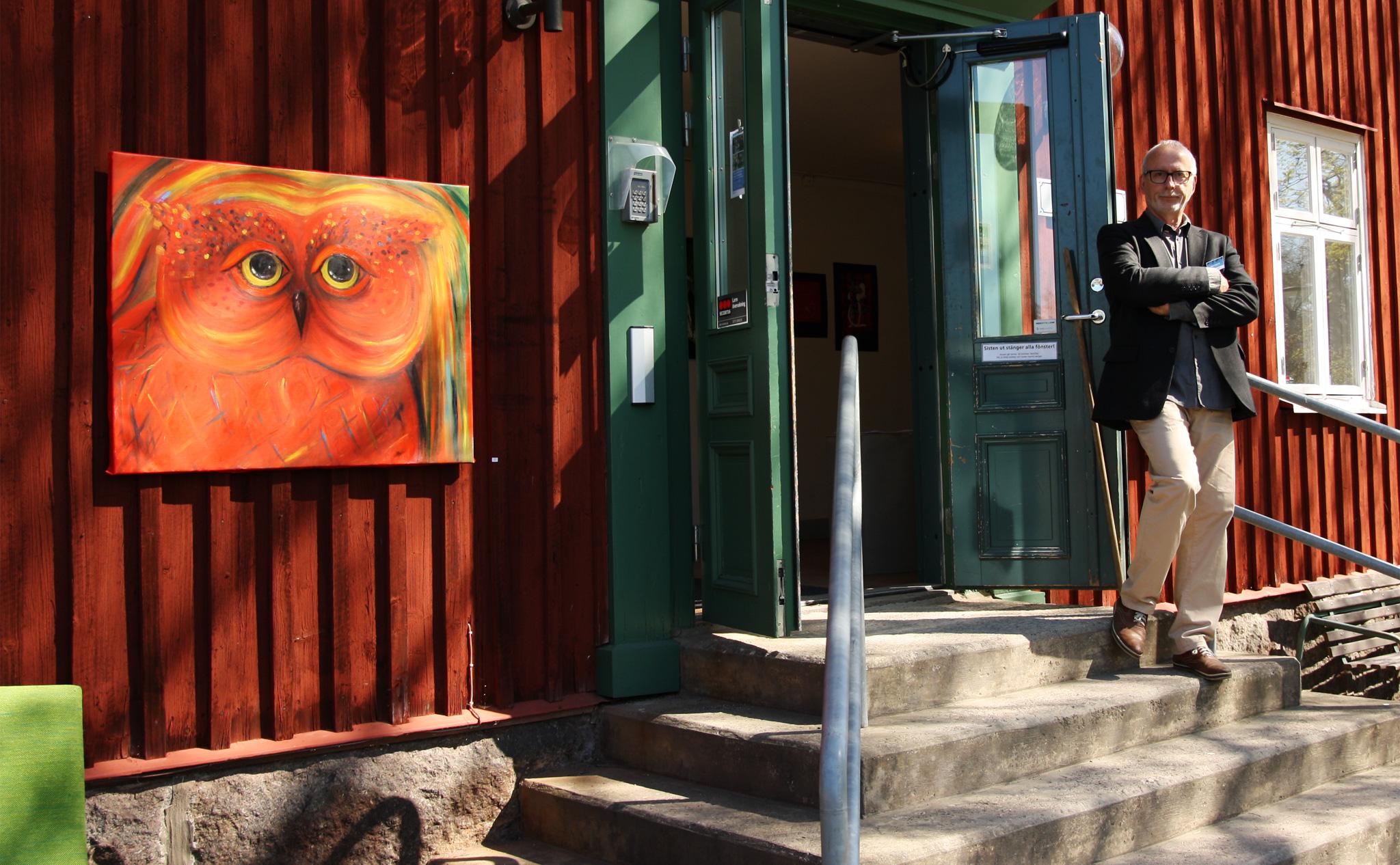 Konsthusets dörrar står öppna, en lärare stå utanför. På husets fasad hänger en röd tavla med en målad fågel.