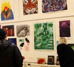 Två personer som tittar på en vägg full av tavlor och målningar.