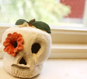 En dödskalle i keramik, med en blomma i ena ögat.