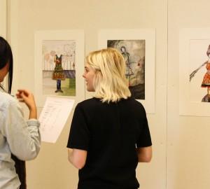 Tre personer tittar på teckningar som hänger på väggen.