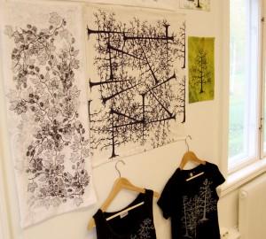 En samling tygtryck och två t-shirts hänger på en vägg.