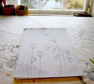 Teckning i ett ritblock som ligger på ett bord framför ett fönster.