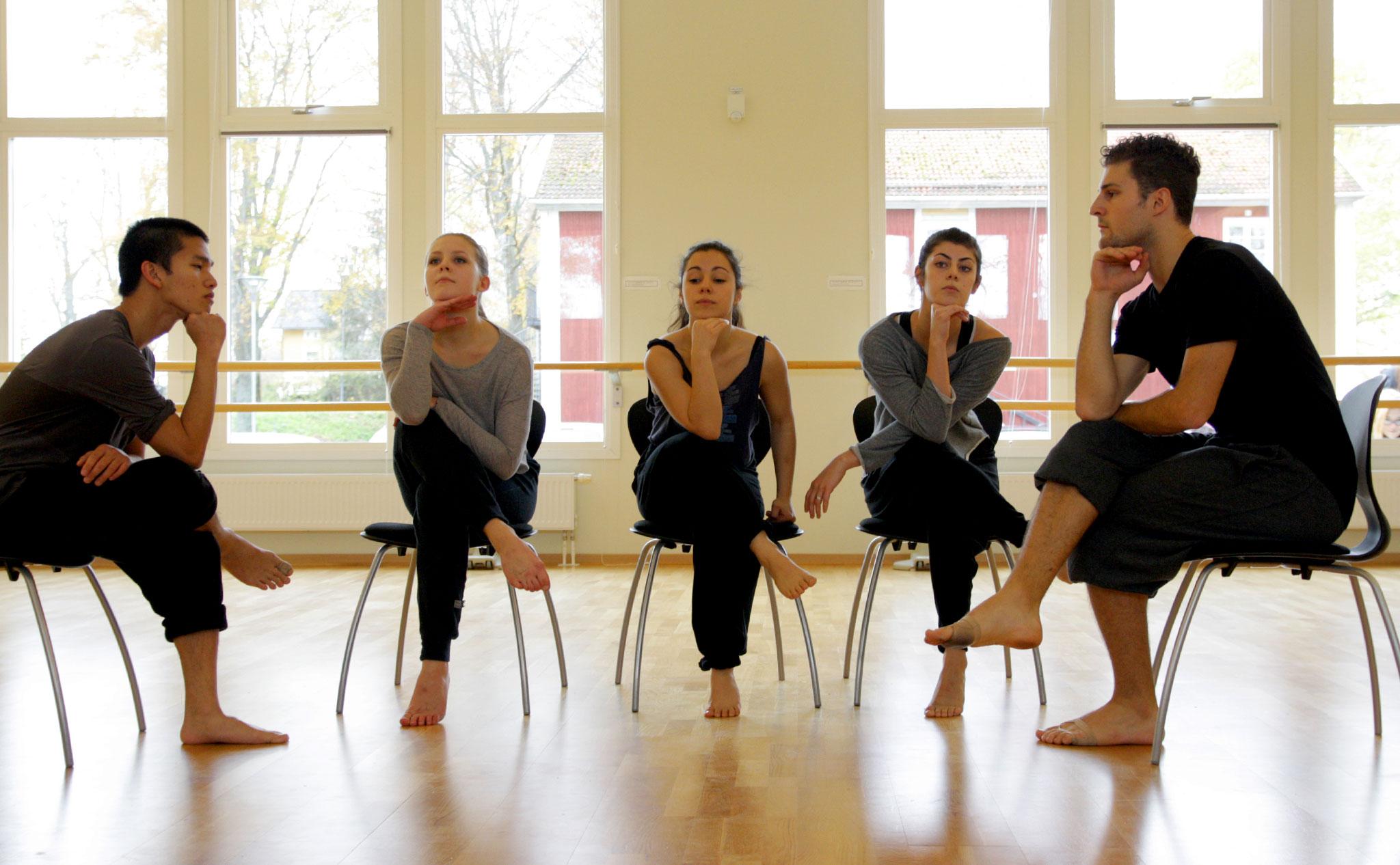 Fem dansare sitter på varsin stol. Korsade ben, armbågarna på knät och hakan i handen.