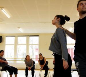 I förgrunden två dansare, den ena med handen på den andres axel. Dom tittar bort från varandra. Tre personer sitter på stolar i bakgrunden.