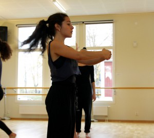 Dansare med sidan mot kameran. Båda händerna utsträcka framför sig och formar en korg.