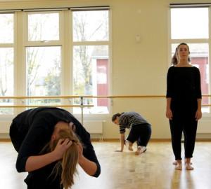 Tre dansare. En i förgrunden i en böjd position med händerna på huvudet.