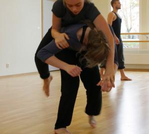 En dansare ligger på mage över en annans rygg.