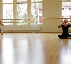En dansare mitt i ett steg till vänster i bild. Till höger en som sitter med korslagda ben och händerna för ögonen. Bredvid en som står rakt med händerna på ryggen.