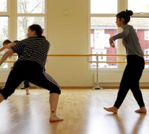 Tre dansare mitt i rörelser över golvet.