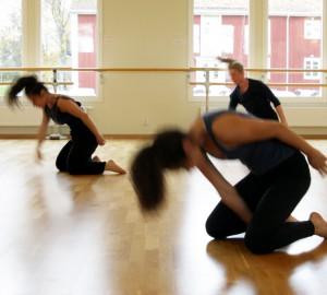 Dansare på väg upp fån knäsittande till stående. Suddiga rörelser.
